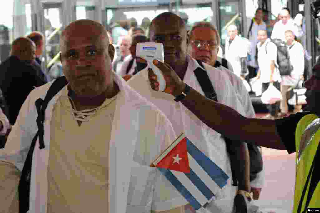 Cuban health workers have their temperatures taken upon arrival at Roberts International Airport outside Monrovia, Liberia, Oct. 22, 2014.