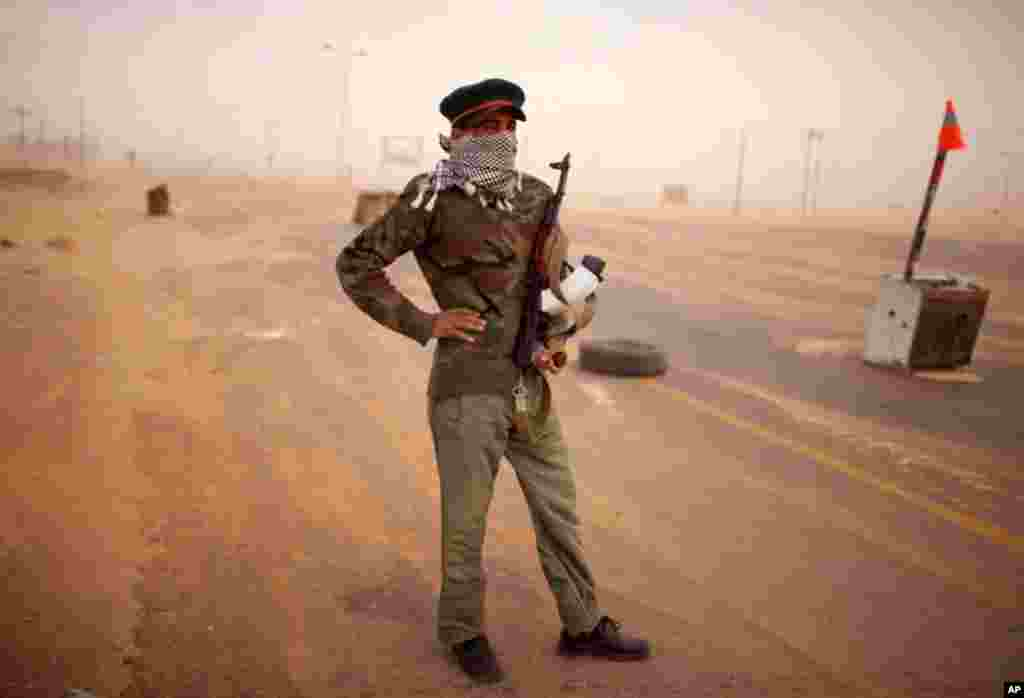 May 11: A rebel soldier stands guard at a windswept check point on the outskirts of Benghazi, Libya. (AP Photo/Rodrigo Abd)