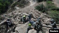 La police paramilitaire transporte une victime après le séisme dans le comté de Jiuzhaigou, à Sichuan, Chine, 9 août 2017.