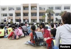 Estudiantes sentados en un patio de recreo después de ser evacuados del edificio escolar tras un terremoto en Ikeda, Osaka, oeste de Japan, el lunes, 18 de junio de 2018.