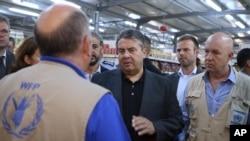 German Economy Minister Sigmar Gabriel, center, visits a supermarket at the Zaatari refugee camp near Mafraq, north of Amman, Jordan, Sept. 22, 2015.