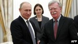 El presidente ruso Vladimir Putin le da la mano a al Asesor de Seguridad Nacional de EE.UU., John Bolton, durante una reunión en el Kremlin en Moscú el 23 de octubre de 2018.