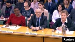 Oxfam's chief executive Mark Goldring, center, Oxfam's international director Winnie Byanyima (left) and Oxfam's chair Caroline Thomson attend a hearing of the British parliament's International Development Committee in London, Britain, Feb. 20, 2018. (REUTERS/Parliament TV handout)