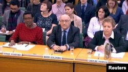Oxfam's chief executive Mark Goldring, center, Oxfam's international director Winnie Byanyima (left) and Oxfam's chair Caroline Thomson attend a hearing of the British parliament's International Development Committee in London, Britain, Feb. 20, 2018.