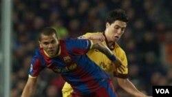 Dani Alves (kiri) beraksi ketika melawan Arsenal dalam Liga Champions. Barcelona melaju ke perempat final.