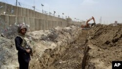 FILE - A Pakistani border guard stands guard as an excavator digs a trench along the Pakistan-Afghanistan border at Chaman post in Pakistan, May, 16, 2014.
