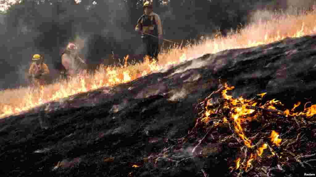 """Bombeiros tentam cavar uma """"linha de fogo"""" no condado de Rocky Lake, Califórnia, 30 de Julho 2015."""