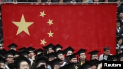Chinese students attend their college graduation ceremony in Shanghai's Fudan University July 2, 2011. Chinese media has reported on recent cases of Chinese university students informing on their professors. (REUTERS/Carlos Barria)