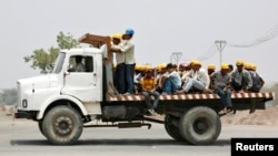 FILE - Workers are transported on a truck during their lunch break at the construction site of a commercial and residential complex on the outskirts of the western Indian city of Ahmedabad, Apr. 22, 2013.