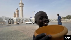 FILE - A young talibe raises a begging bowl in front of the grand mosque in Touba, in the central region of Senegal, Feb. 23, 2012.