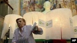 Seorang wanita meninggalkan kotak suaranya di sebuah TPS di Tbilisi, Georgia (1/10). Warga Georgia mengikuti pemilu parlemen yang akan menentukan masa depan pemerintahan presiden Saakashvili (AP Photo/Shakh Aivazov)