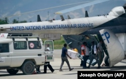 People load emergency supplies from a Doctors Without Borders ambulance into a United Nations helicopter bound for the earthquake ravaged city Les Cayes, at the local terminal of the Toussaint Louverture airport in Port-au-Prince, Haiti, Sunday, Aug. 15,