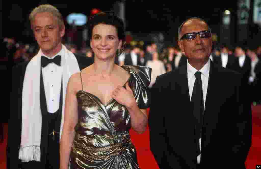 """امسال عباس کیارستمی کارگردان فقید ایران غایب بزرگ جشنواره ونیز است. عکسی از سال ۲۰۱۰، او به همراه ژولیت بینوش، بازیگر فرانسوی فیلم """"کپی برابر اصل"""" و ویلیام شیمر، خواننده انگلیسی اپرا که بازیگر این فیلم بود."""