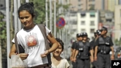***File*** A woman and a child walk ahead of police officers patrolling on a street in Urumqi in northwest China's Xinjiang Uygur Autonomous Region Friday, July 2, 2010. Chinese authorities have stepped up security measures ahead of the anniversary of a d