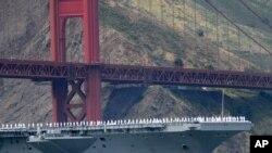 Los marineros del portaviones USS Nimitz saludan desde el puente de la nave al pasar bajo el puente Golden Gate durante la celebración del 75 aniversario.