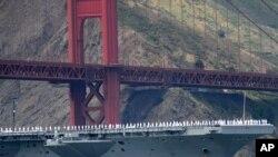 ملوانان روی عرشه کشتی USS Nimitz در حال عبور از زیر پل گلدن گیت به مناسبت هفتاد و پنجمین سال ساخت پل - مه ۲۰۱۲