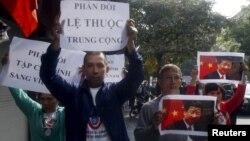 Người biểu tình cầm hình ảnh và biểu ngữ trong cuộc biểu tình chống Trung Quốc tại Hà Nội, ngày 3/11/2015.