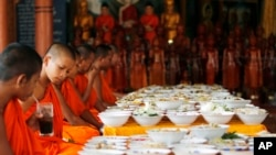 Local Buddhist monks prepare to eat food made by villagers and donated as offerings to the dead during celebrations of Pchum Ben, or Ancestors' Day, at a Buddhist pagoda of Wat Kanty Yaram, in Prek Thoang village, Kandal province, northeast of Phnom Penh, Cambodia Wednesday, Sept. 17, 2014. The traditional 15-day festival, which commemorates the spirits of the dead, began on Sept. 9. (AP Photo/Heng Sinith)