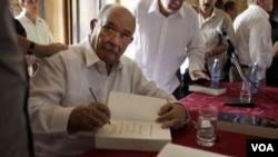 """D' Escoto autografiando ejemplares de su libro """"Antiimperialismo y no violencia"""" en La Habana."""