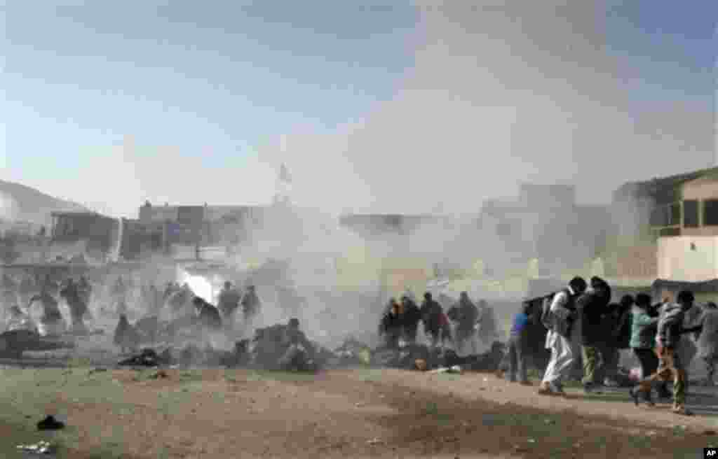 EDS NOTE: GRAPHIC CONTENT - Smoke and dust rises at the scene of a suicide attack which struck a Muharram procession in Kabul, Afghanistan, Tuesday, Dec. 6, 2011. A suicide bomber struck a crowd of Shiite worshippers marking a holy day Tuesday in the Afgh