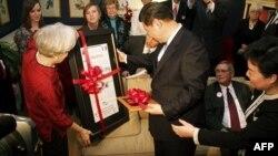 Bà Sarah Lande trao tặng Phó Chủ tịch Trung Quốc một bản sao của tờ báo Journal Muscatine từ năm 1985, là lần đầu tiên ông Tập đến thăm thị trấn Muscatine, bang Iowa
