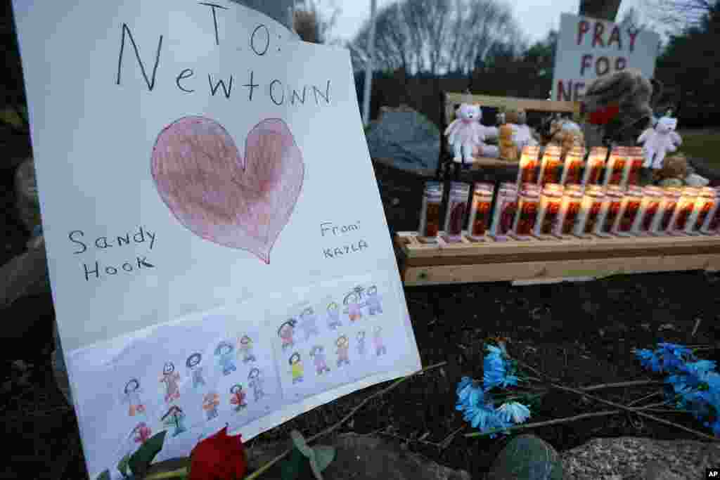 A child's message rests with a memorial for shooting victims, December 16, 2012, in Newtown, Conn.