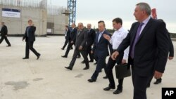 From right: Vice Premier Dmitry Rogozin, Russian Space Agency chief Oleg Ostapenko, Russian President Vladimir Putin walk during a visit to a construction site of Vostochny Cosmodrome, in the Amur region, Russia, Sept. 2, 2014.
