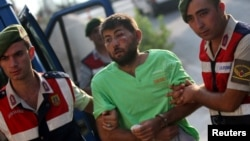 土耳其宪兵队押送在上个月未遂政变中试图捉拿埃尔多安总统的11名突击队员中的一人前往穆拉省一警察总部。(2016年8月1日)