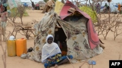 FILE - A woman is seen sitting in front of a tent in the Assaga refugee camp, set up by the U.N. for Nigerian refugees who fled to southeast Niger to escape Boko Haram militants, Sept. 16, 2015.