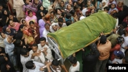 Relatives and residents carry the coffin of a woman who was killed in a deadly blaze at a garment factory in Karachi, Pakistan, September 13, 2012.