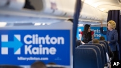 Hillary Clinton speaks with senior aide Huma Abedin (L) aboard her campaign plane at an airport in White Plains, New York, Oct. 28, 2016. The FBI found the potentially incriminating emails on a computer Abedin shared with her estranged husband.