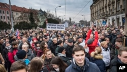 """Protesters hold a banner reading """"I do care about it"""" during a mass quiet march in Bratislava, Slovakia, March 23, 2018. Many thousands of Slovaks took to the streets in anti-government protests amid a continuing political crisis triggered by the recent slayings of an investigative reporter and his fiancee."""