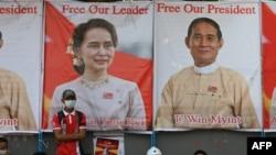 រូបឯកសារ៖ ក្រុមអ្នកតវ៉ា កាន់បដានិងបង្ហាញរូបភាពនៃមេដឹកនាំស៊ីវិល គឺអ្នកស្រី Aung San Suu Kyi (ឆ្វេង) ដែលត្រូវបានបណ្តេញចេញពីតំណែង នៅពេលពួកគេចូលរួមធ្វើបាតុកម្មប្រឆាំងនឹងរដ្ឋប្រហារយោធានៅមុខស្ថានទូតចិន ក្នុងទីក្រុងរ៉ង់ហ្គូននៅថ្ងៃទី២១ ខែកុម្ភៈ ឆ្នាំ២០២១។