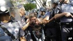 Polisi menahan demonstran dalam protes publik yang menuntut layanan publik yang lebih baik dan menolak anggaran membludak untuk Piala Dunia, Juni 2014. (AP/Nelson Antoine)
