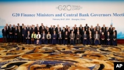 Officials led by host country officials Chinese Finance Minister Lou Jiwei, center left in front, and People's Bank of China Governor Zhou Xiaochuan, center right in front, pose for a family photo of G20 Finance Ministers and Central Bank Governors Meeting at the Pudong Shangri-la Hotel in Shanghai, Feb. 27, 2016.