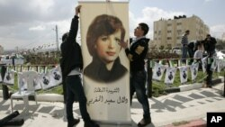 FILE - Palestinians inaugurate a square to commemorate Dalal Mughrabi, a Palestinian female militant who killed dozens of civilians in a 1978 bus hijacking in Israel, seen on a banner, in the West Bank city of Ramallah, March 13, 2011. Norway is now demanding the Palestinian Authority return a donation Oslo made to a women's center on the West Bank because the center was named after Mughrabi.