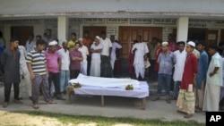 살해된 노동자의 시신을 담을 관 주변에 모여 있는 지역 주민들