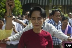 FILE - Myanmar opposition leader and head of the National League for Democracy (NLD) Aung San Suu Kyi (C) visits a polling station in Kawhmu township, Yangon, Nov. 8, 2015.