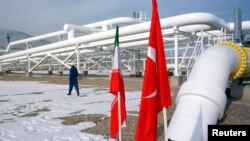 A worker walks past the pumping station on the border between Iran and Turkey during the inauguration ceremony for the Iran-Turkey gas pipeline, January 22, 2002.