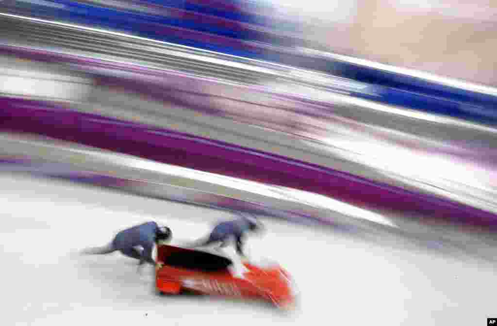 The two-man team from Monaco MON-1, piloted by Patrice Servelle, start a run during a training session for the men's two-man bobsled at the 2014 Winter Olympics, Feb. 14, 2014.