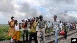 Villagers carry an injured person after a train ran over a group of Hindu pilgrims at a crowded station in Dhamara Ghat, Bihar state, India, August 19, 2013.