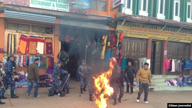 Nepalese police react to a Tibetan exile who set himself on fire in Kathmandu, February 13, 2013.