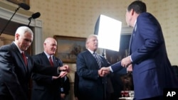 FILE - Vice President Mike Pence, left, and Secret Service Director Joseph Clancy stand as President Donald Trump shakes hands with FBI Director James Comey during a reception for inaugural law enforcement officers and first responders Jan. 22, 2017.