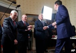 FILE - Vice President Mike Pence, left, and Secret Service Director Joseph Clancy stand as President Donald Trump shakes hands with FBI Director James Comey during a reception for inaugural law enforcement officers and first responders in the Blue Room of the White House.