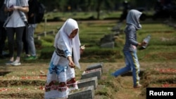 A girl places flowers on the graves of some of the victims who died during the political turmoil of 1998 during a 20th anniversary commemoration at Pondok Ranggon mass grave in Jakarta, Indonesia, May 13, 2018.