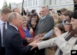 FILE - Russian President Vladimir Putin, left, greets local citizens in Omsk, Russia, Aug. 28, 2018.