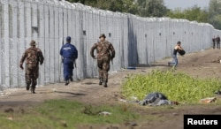 A migrant crosses the boarder fence as soldiers and police try to catch him close to a migrant collection point in Roszke, Hungary, Sept. 12, 2015.