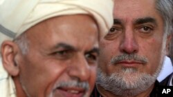 FILE - Afghanistan Chief Executive Abdullah Abdullah, right, listens as President Ashraf Ghani speaks at the presidential palace in Kabul, Oct. 4, 2014,