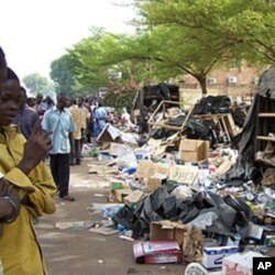 Residents look at debris on the pavement on April 16, 2011 in Ouagadougou after soldiers from three barracks took to the streets of the Burkina Faso capital overnight, firing into the air and pillaging as a mutiny entered its third day