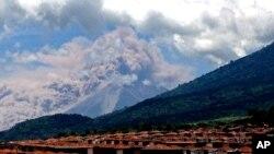 En esta foto tomada con un teléfono celular, el Volcán de Fuego lanza humo y cenizas. La imagen fue captada en el pueblo de Palin, al sur de Ciudad de Guatemala, la capital del país.